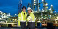 zwei Männer in Schutzkleidung vor einer Raffinerie