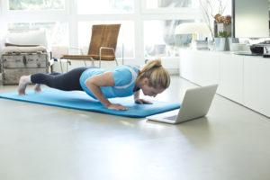 Frau macht Fitnessuebungen im Wohnzimmer