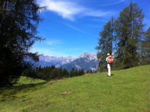 Mann mit Rucksack steht vor einer Bergkulisse