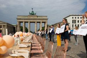 gedeckte Tafel und Demonstranten der Hochzeitsbranche