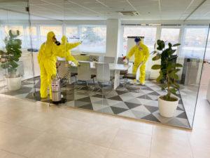 Mitarbeiter in Schutzanzügen desinfizieren einen Innenram