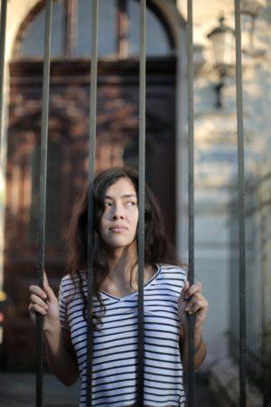 junge Frau schaut durch Gitterzaun