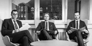 Drei Herren in dunklen Anzügen