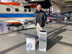 Erfinder Irén Dornier mit dem Filtergerät vor einem Flugzeug