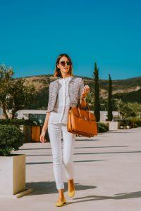 junge Frau mit Laptoptasche aus braunem Leder